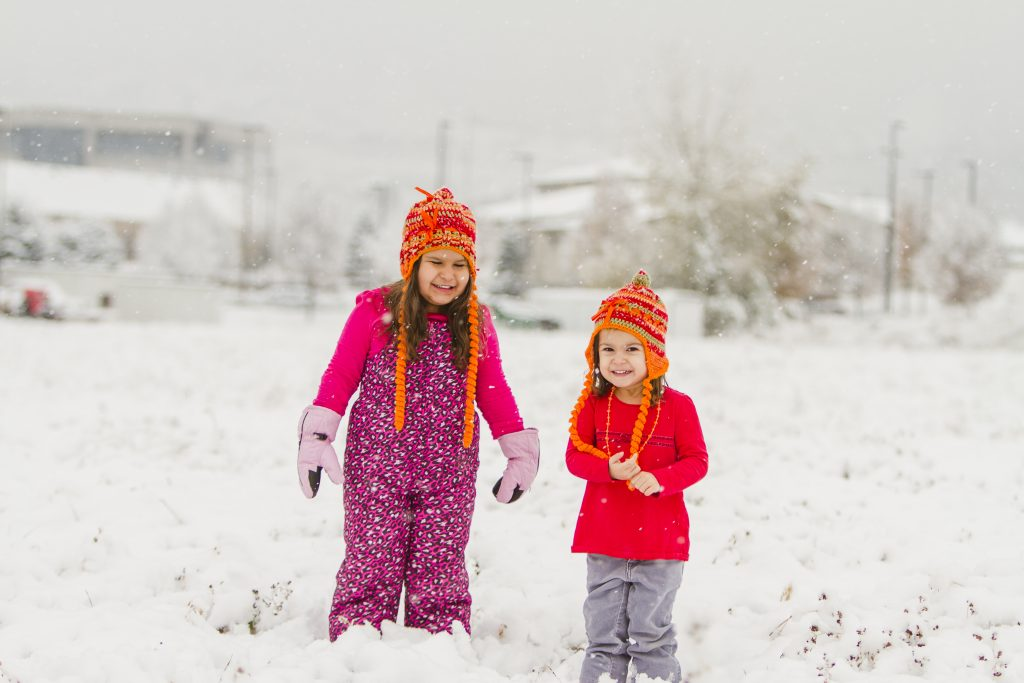 Two girls in snow with beanies